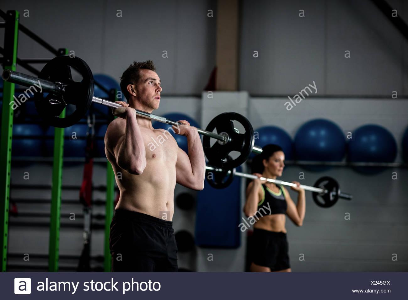 L uomo e la donna il sollevamento barbell Immagini Stock