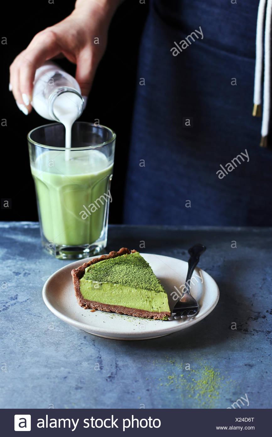 Una fetta di matcha crostata con crema di latte ripieno di formaggio su una piastra.mano femmina versando il latte di cocco in matcha latte sullo sfondo Immagini Stock