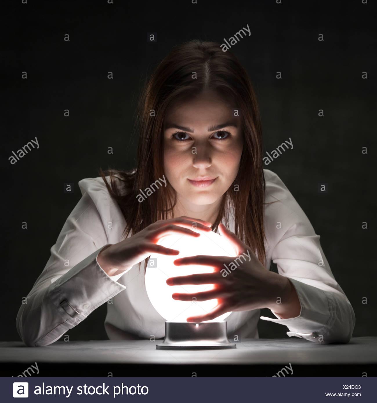 Studio Ritratto di giovane donna azienda sfera di cristallo Immagini Stock