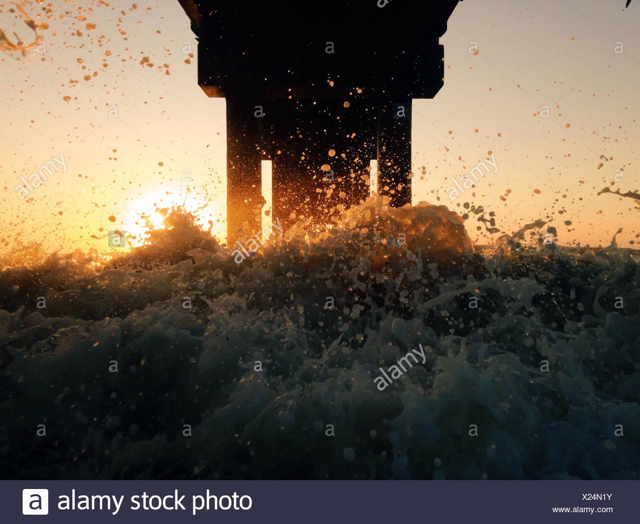 Stati Uniti d'America, Florida, St Augustine Beach, Sunrise sotto il molo con spruzzi e sun flare Immagini Stock