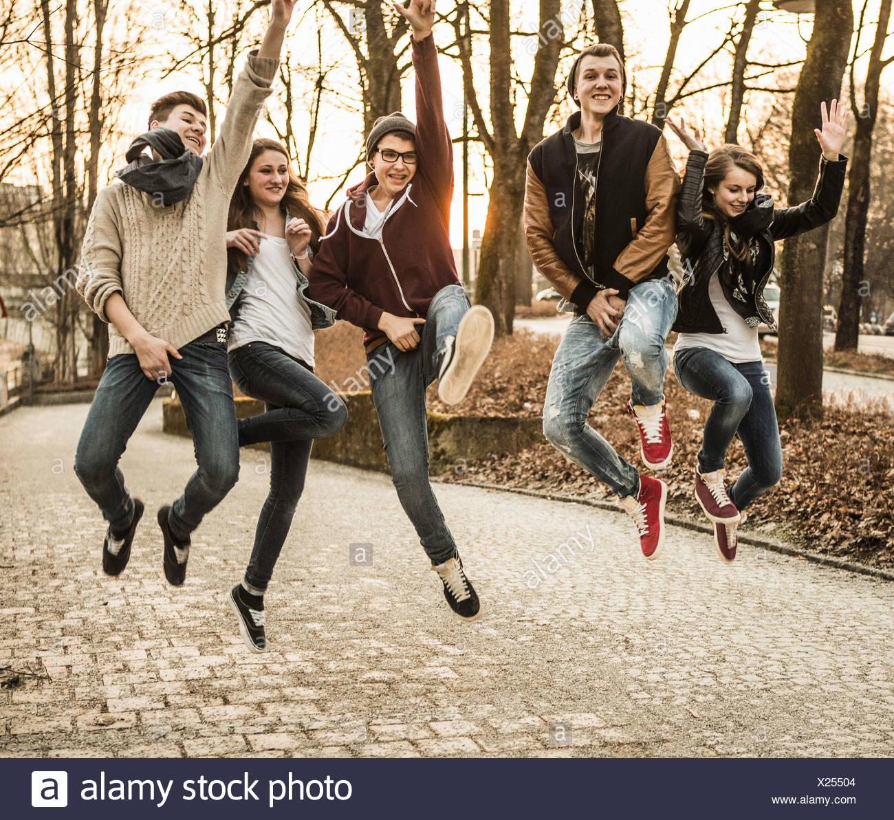 Cinque adolescenti jumping Immagini Stock