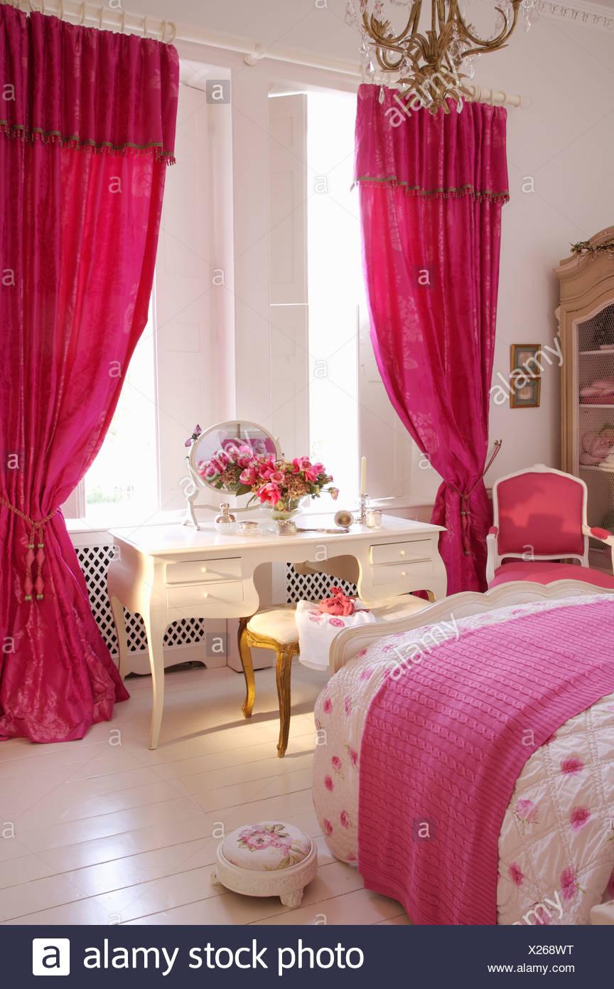 Rosa luminoso tende su finestra sopra white toeletta in camera da ...