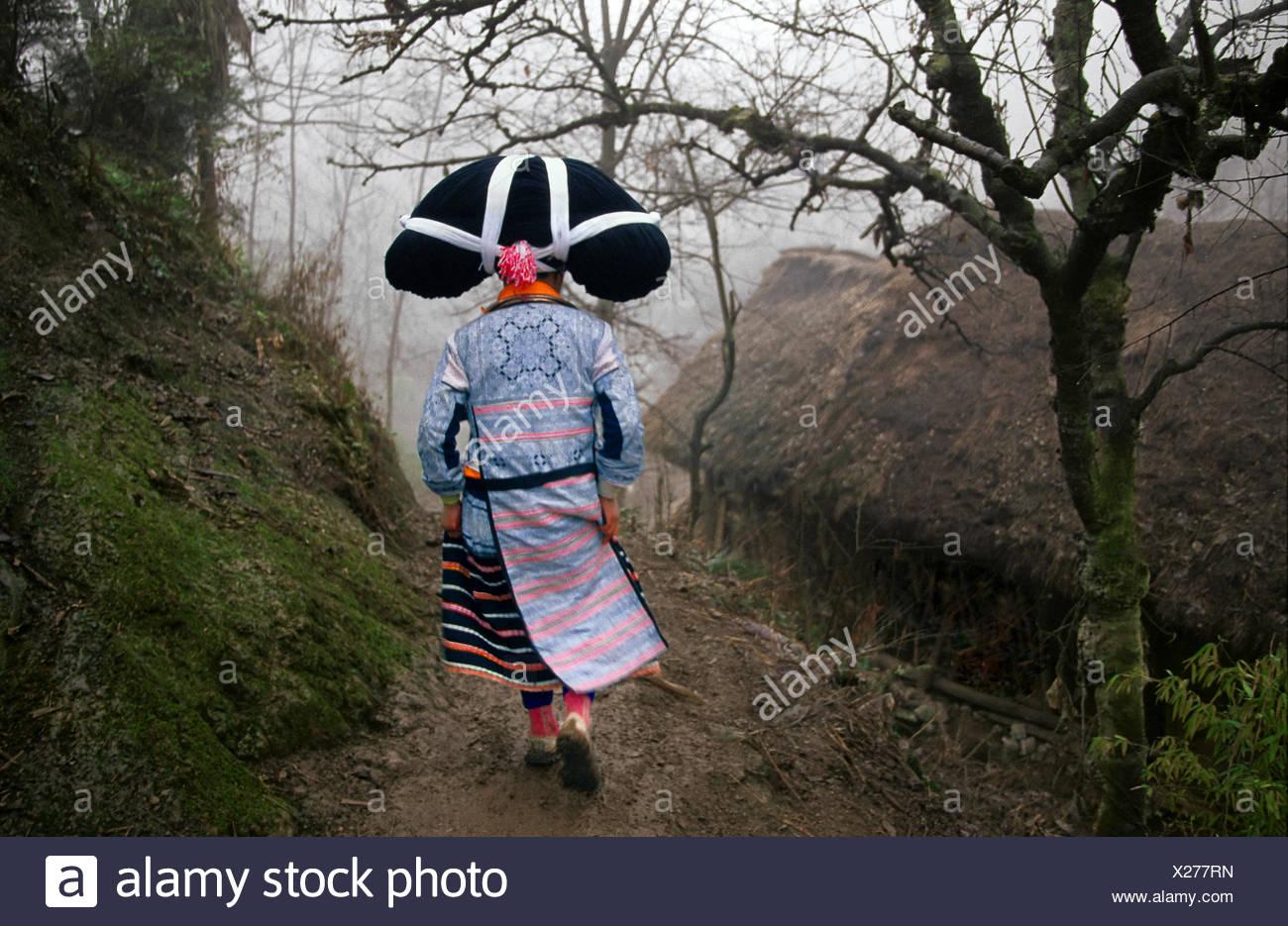 Una donna dalla lunga cornuto Miao minoranza etnica su un sentiero a piedi si prepara per il Lusheng Festa della Primavera. Immagini Stock