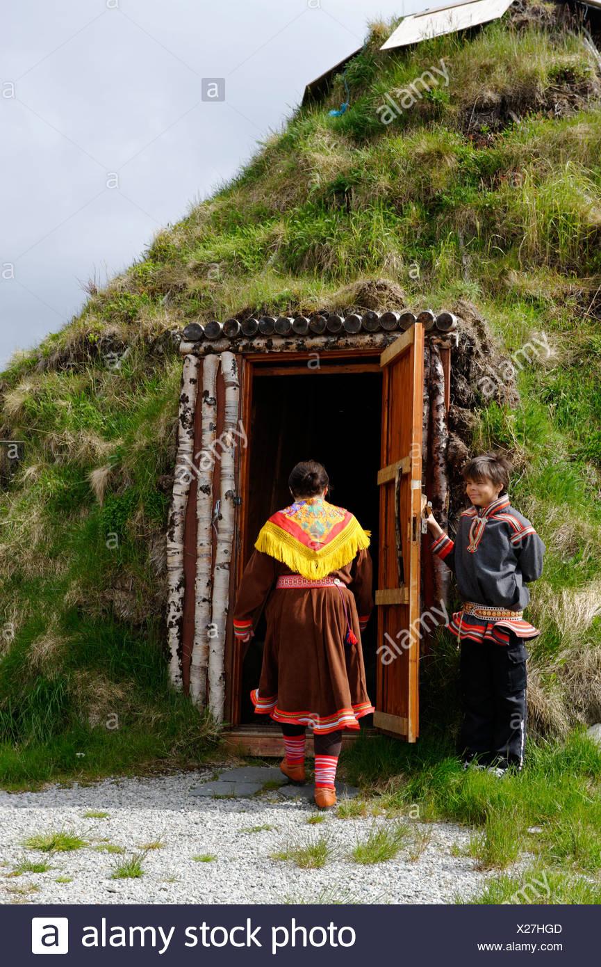 Donna che indossa il costume tradizionale del popolo Sami nella parte anteriore della sua terra coperta lodge, Hammerfest, Norvegia, Scandinavia, Immagini Stock
