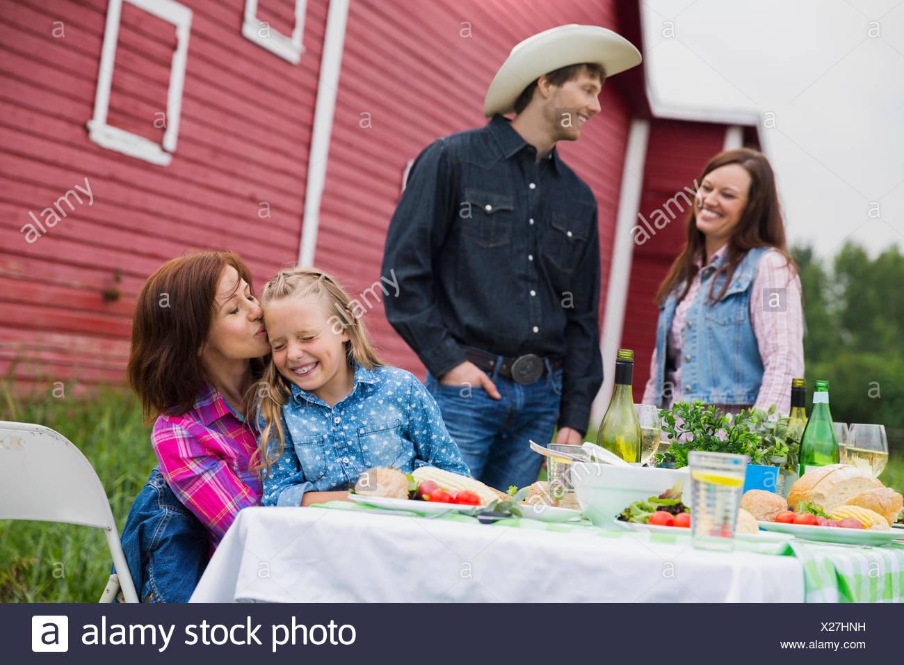 Famiglia di gustare la cena al di fuori di un fienile Immagini Stock