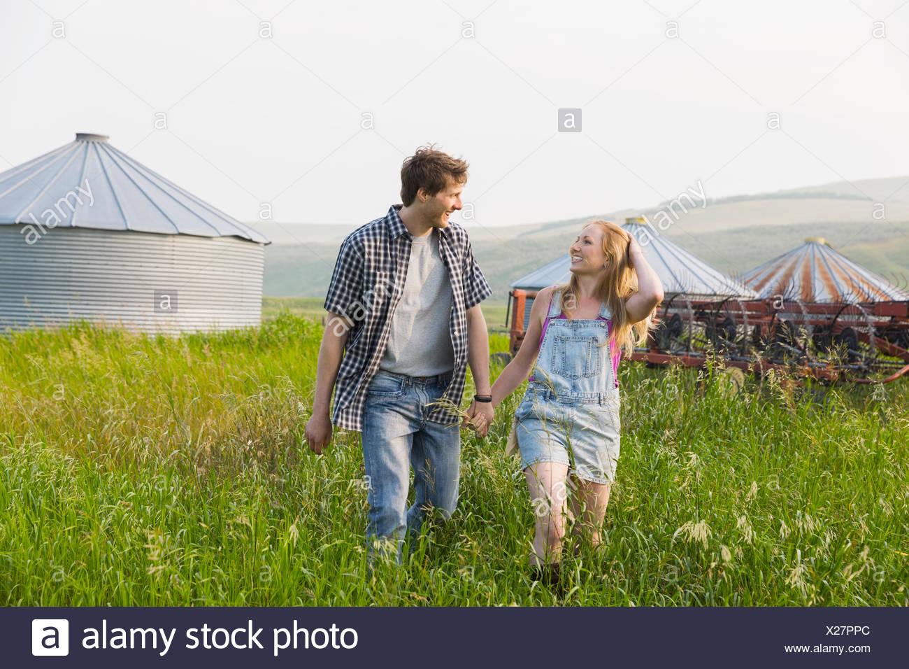 Giovane tenendo le mani e piedi in campo rurale Immagini Stock