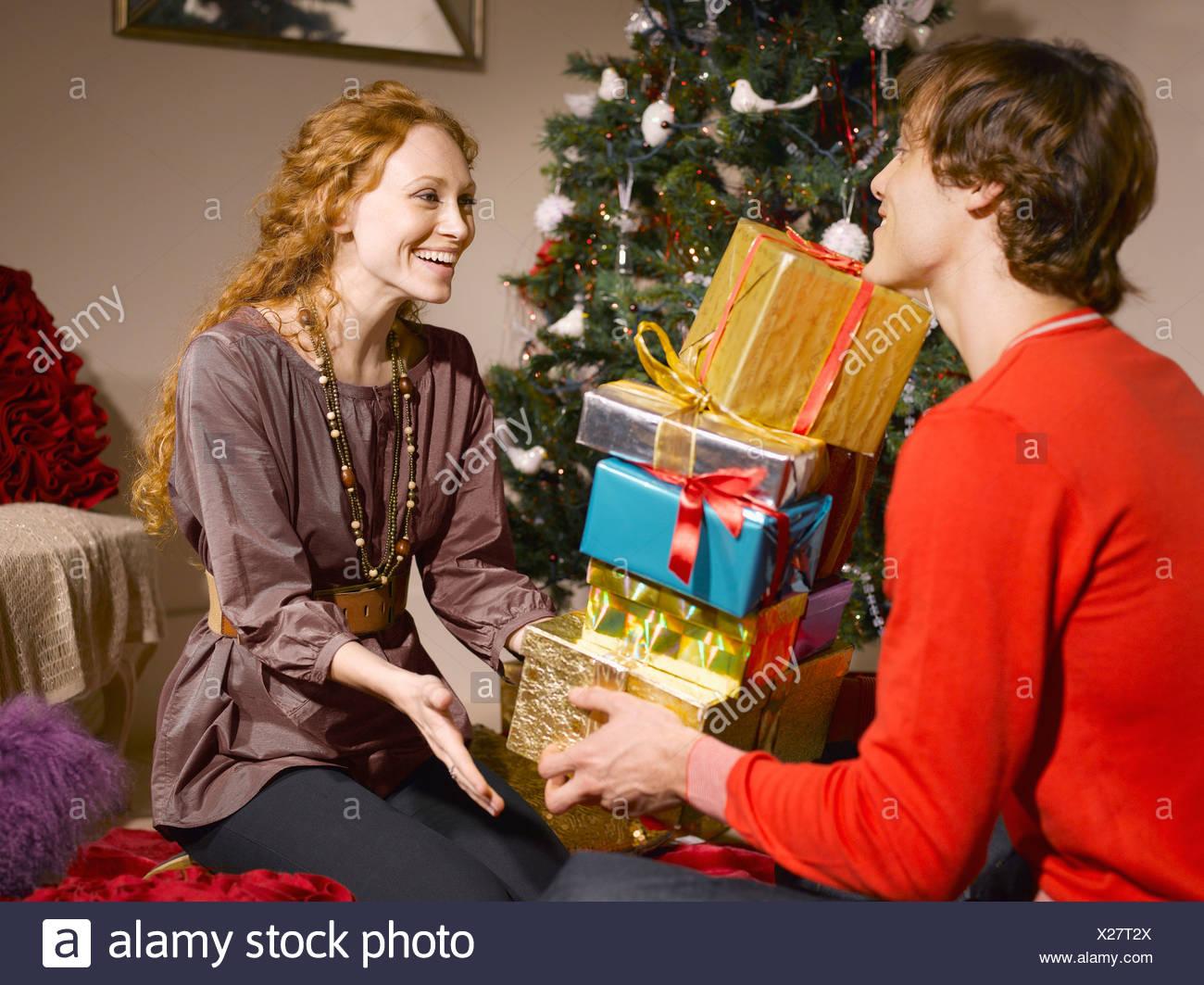 Regali Di Natale Per Moglie.L Uomo Dando Moglie Pila Di Regali Di Natale Foto Immagine Stock