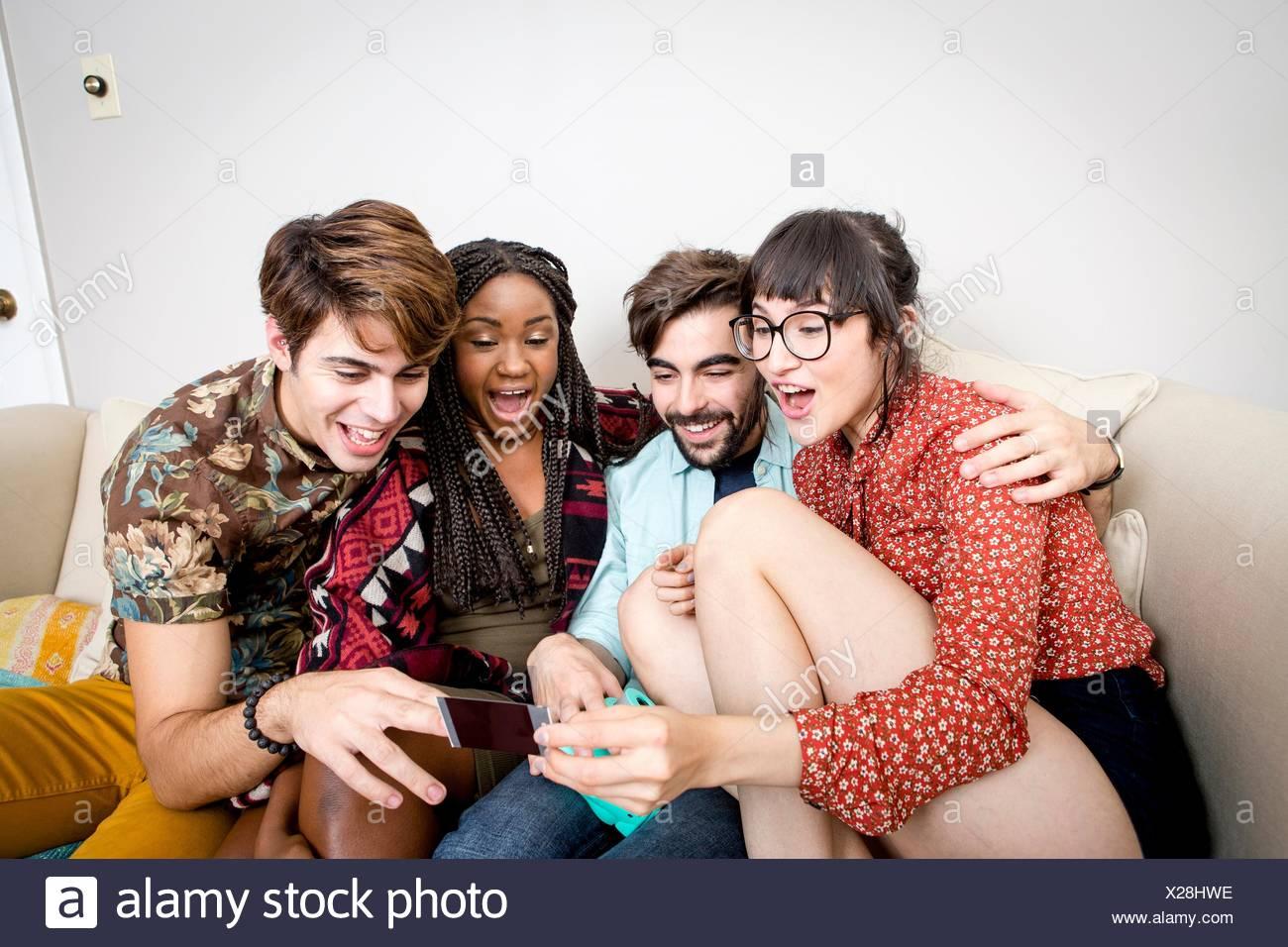 Due giovani coppie hipster seduto sul divano appartamento rideva di fotografia istantanea Immagini Stock