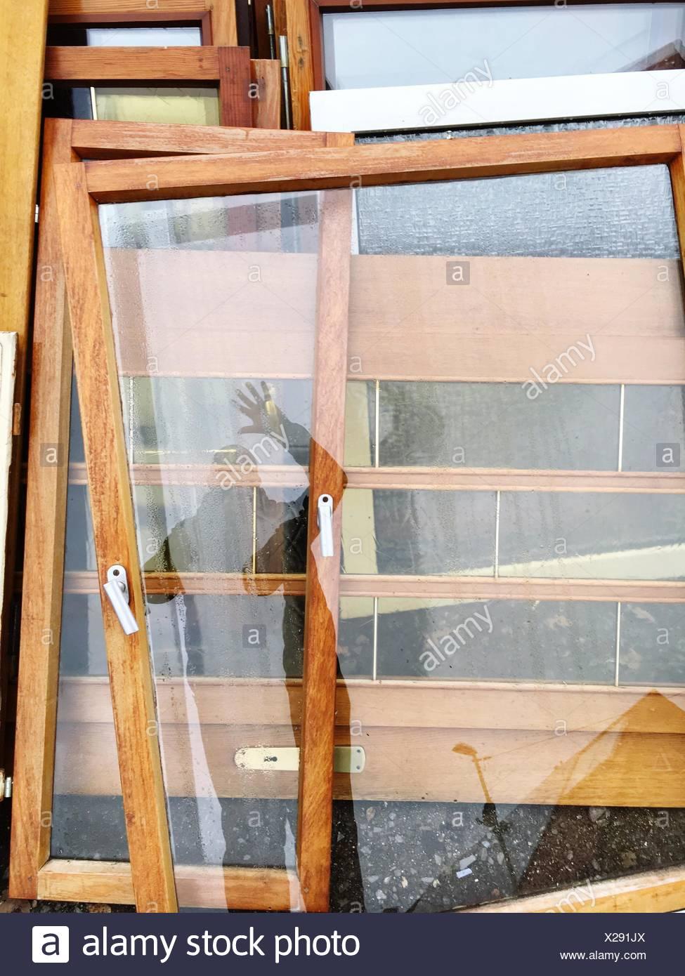 La riflessione di uomo sulla porta di vetro in officina Immagini Stock