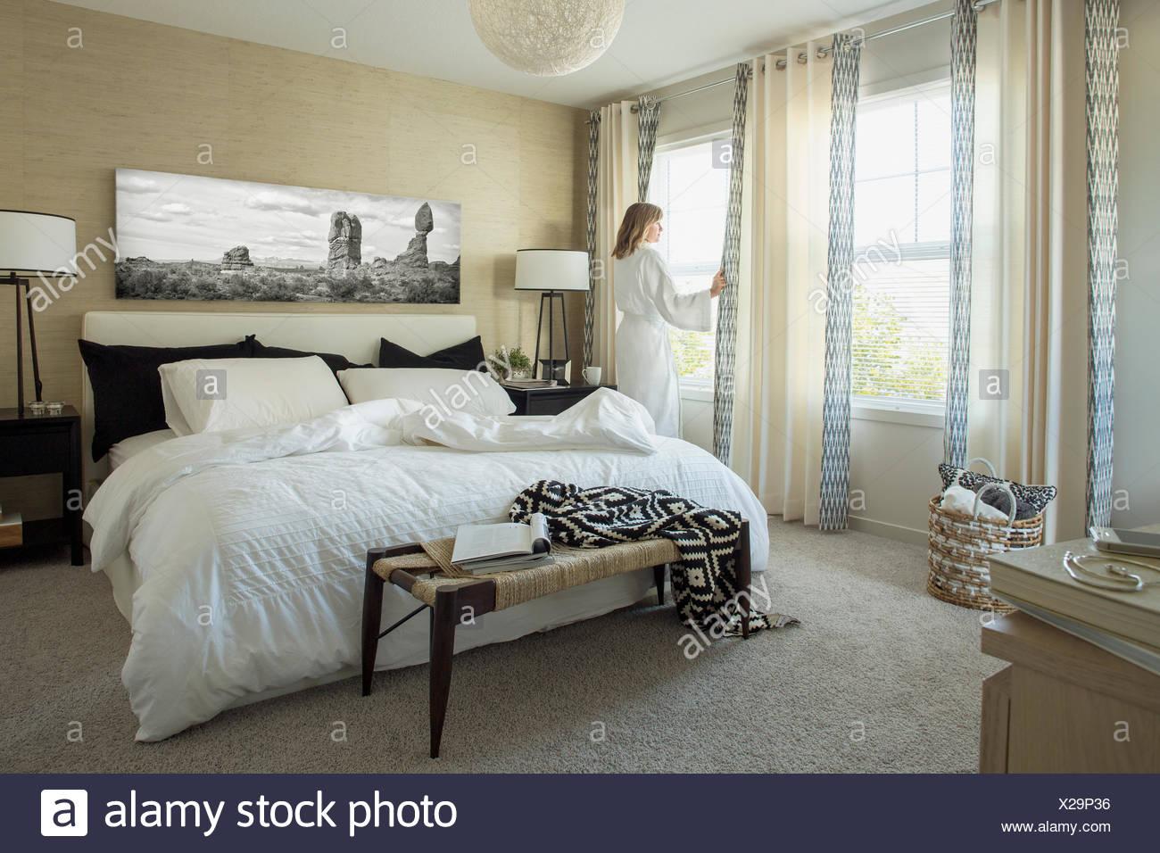 Donna in accappatoio in camera da letto finestra Immagini Stock