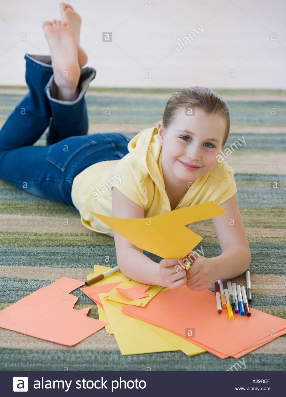 Ragazza il taglio di costruzione della carta sul pavimento Immagini Stock