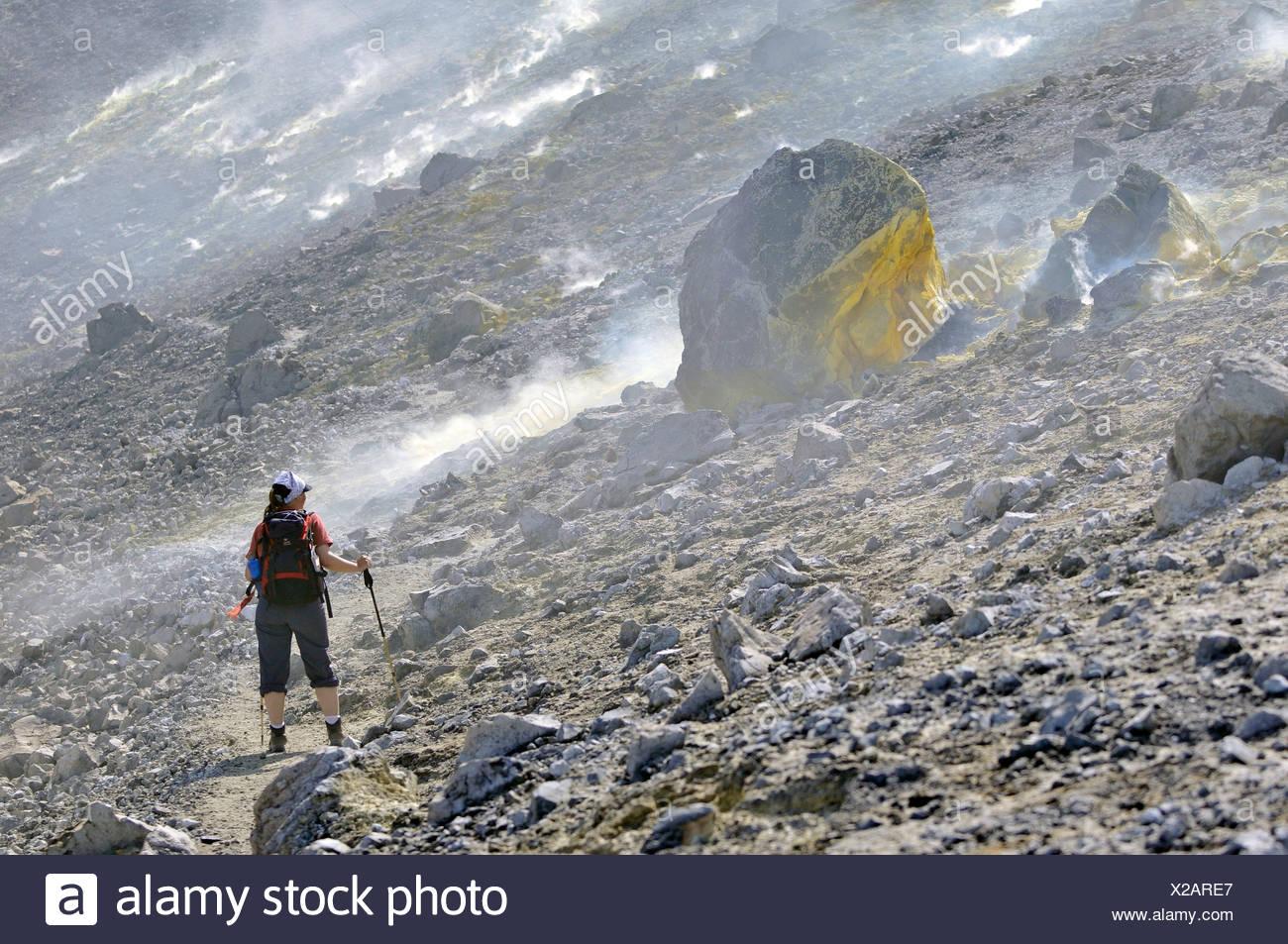 Escursionista trekking attraverso i fumi di zolfo e rocce vulcaniche, isola di Vulcano, Eolie o Lipari Isole, Sicilia, Italia meridionale, Italia Immagini Stock