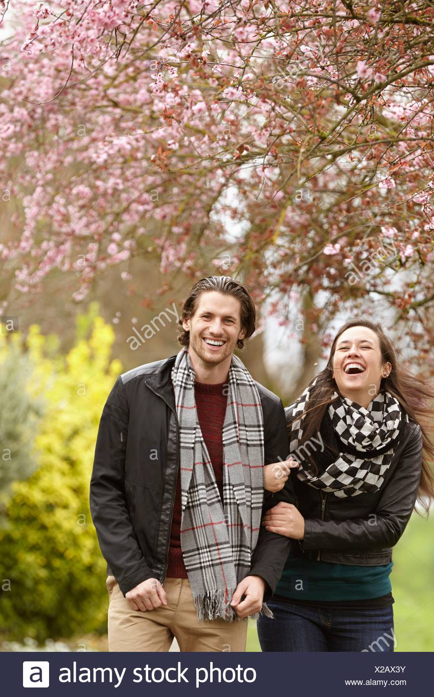 Coppia giovane passeggiare e ridere in posizione di parcheggio Immagini Stock