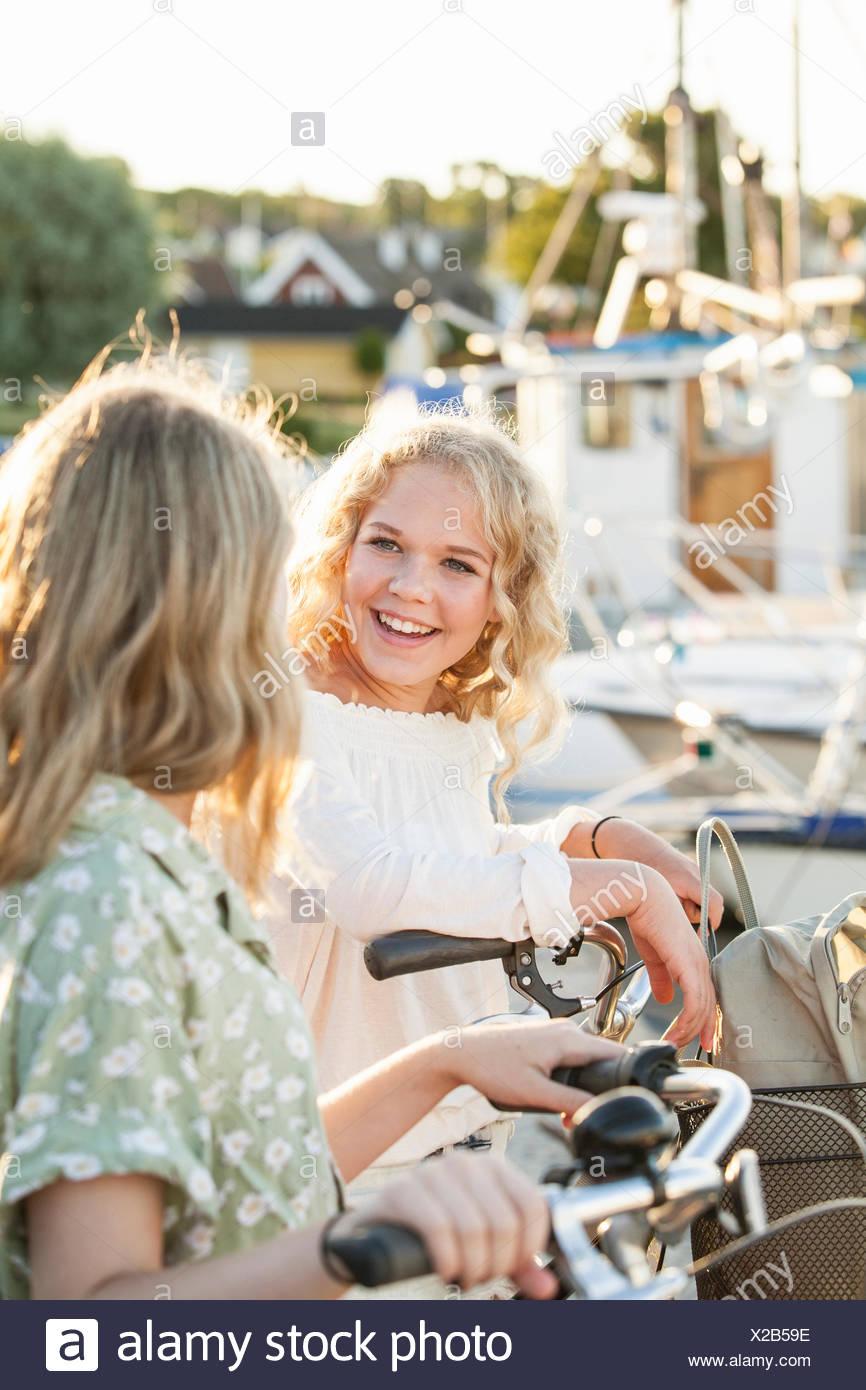 La Svezia, Blekinge, Hallevik, due ragazze adolescenti(14-15, 16-17) con le biciclette presso il marina bay Immagini Stock