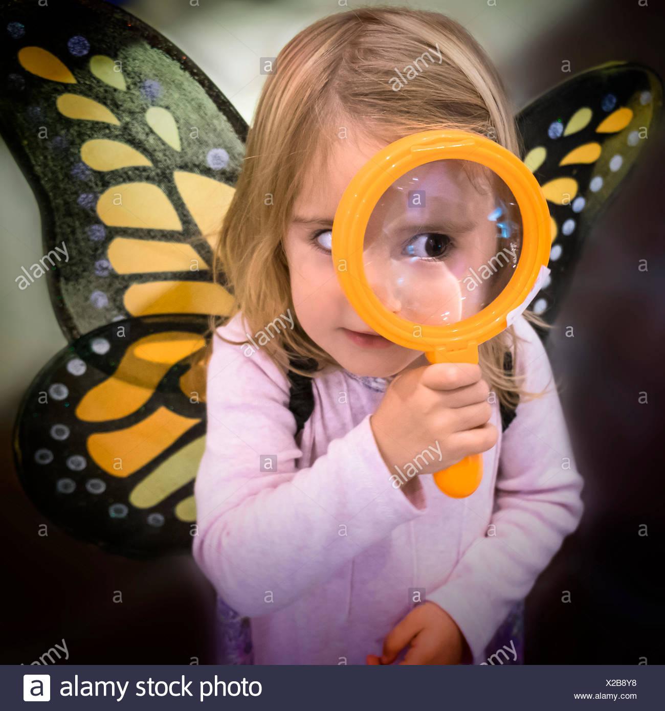 La ragazza (2-3) indossare le ali delle farfalle guardando attraverso la lente di ingrandimento Immagini Stock