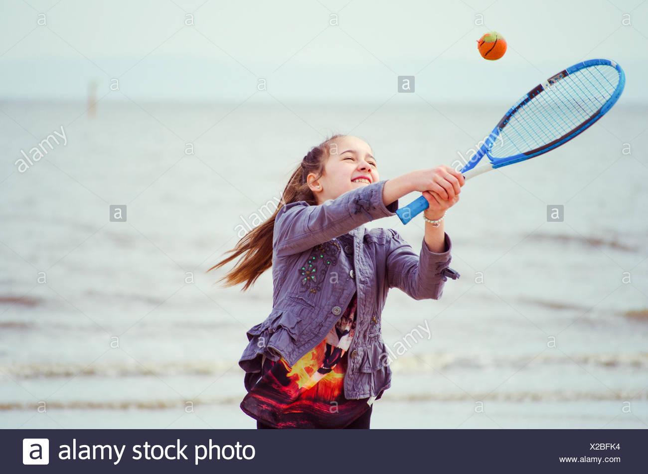 Ragazza giocando a tennis sulla spiaggia Immagini Stock