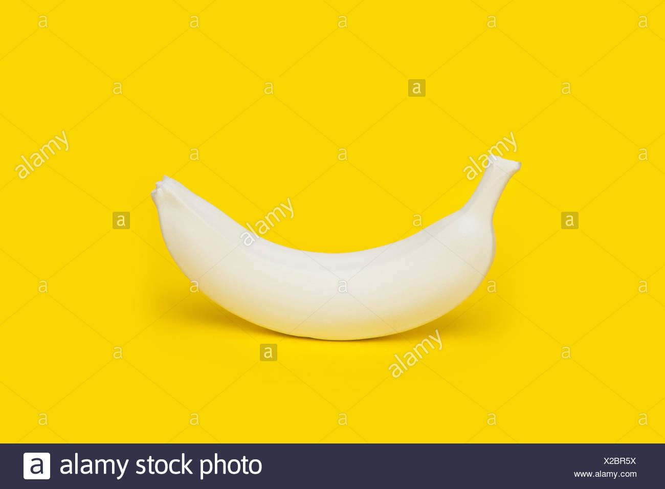 Banana dipinto di bianco su sfondo giallo Immagini Stock