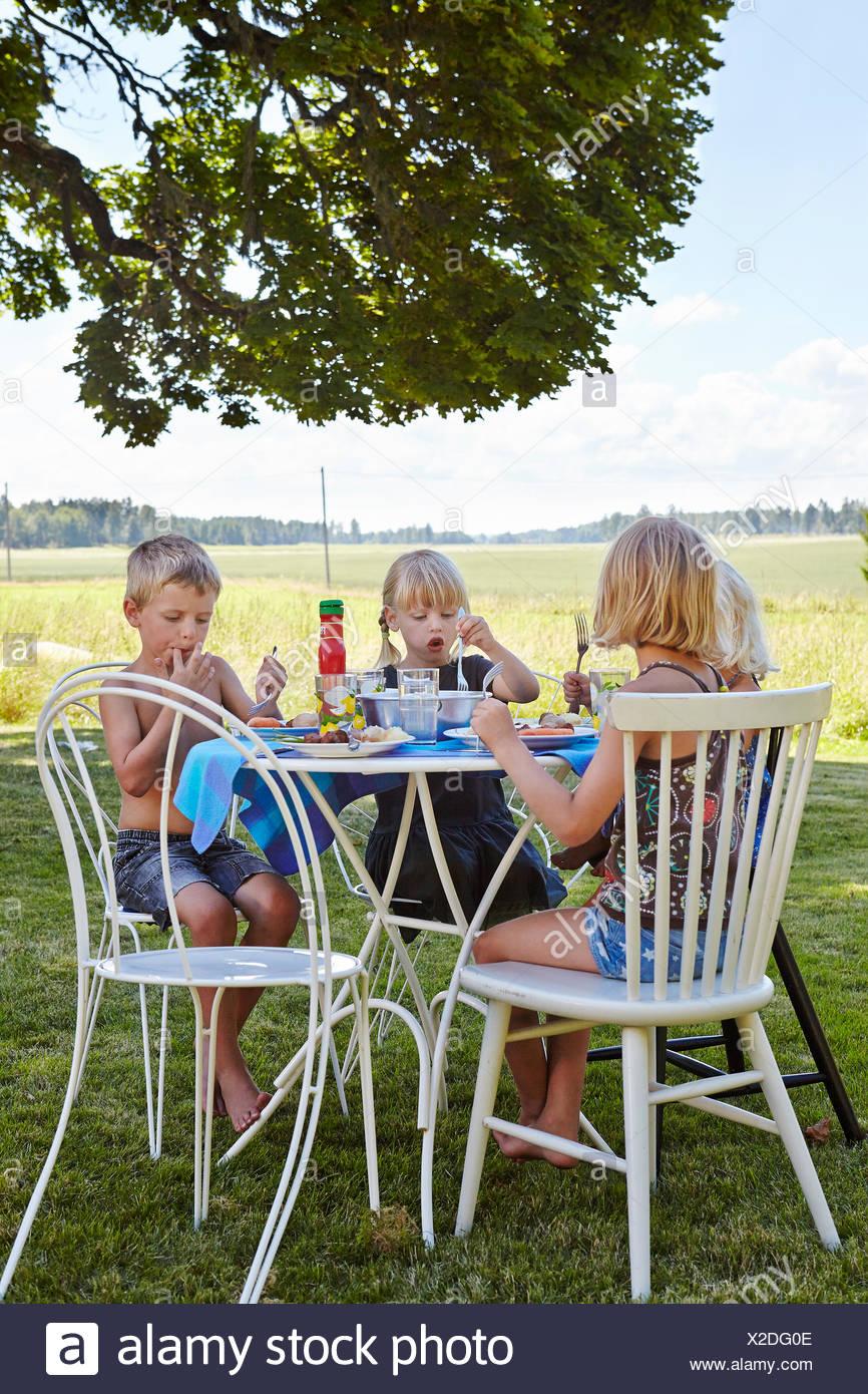 Bambini (4-5, 6-7) di mangiare il pranzo in Prato Immagini Stock