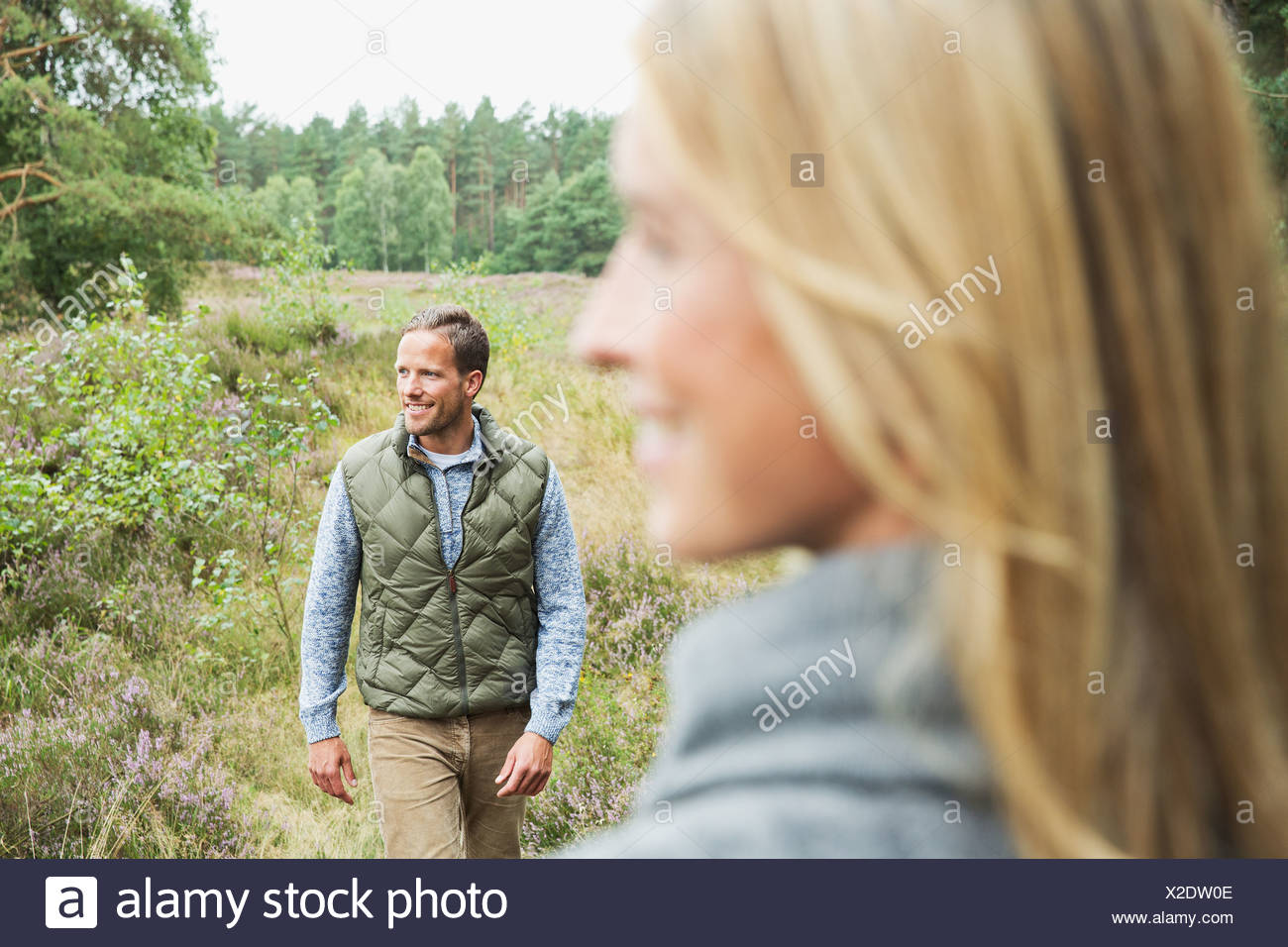 Metà uomo adulto che guarda lontano, donna sfocato in primo piano Immagini Stock