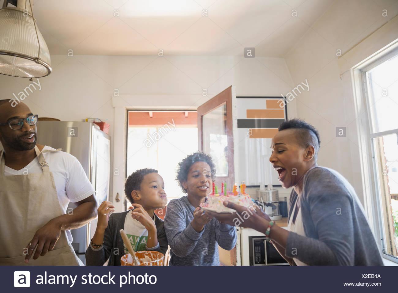 Famiglia guarda la madre soffiare la torta di compleanno candele Immagini Stock