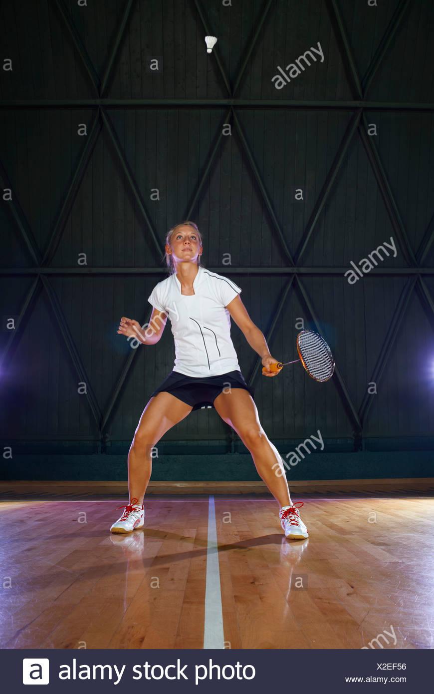 Giovane donna giocando badminton su corte Immagini Stock