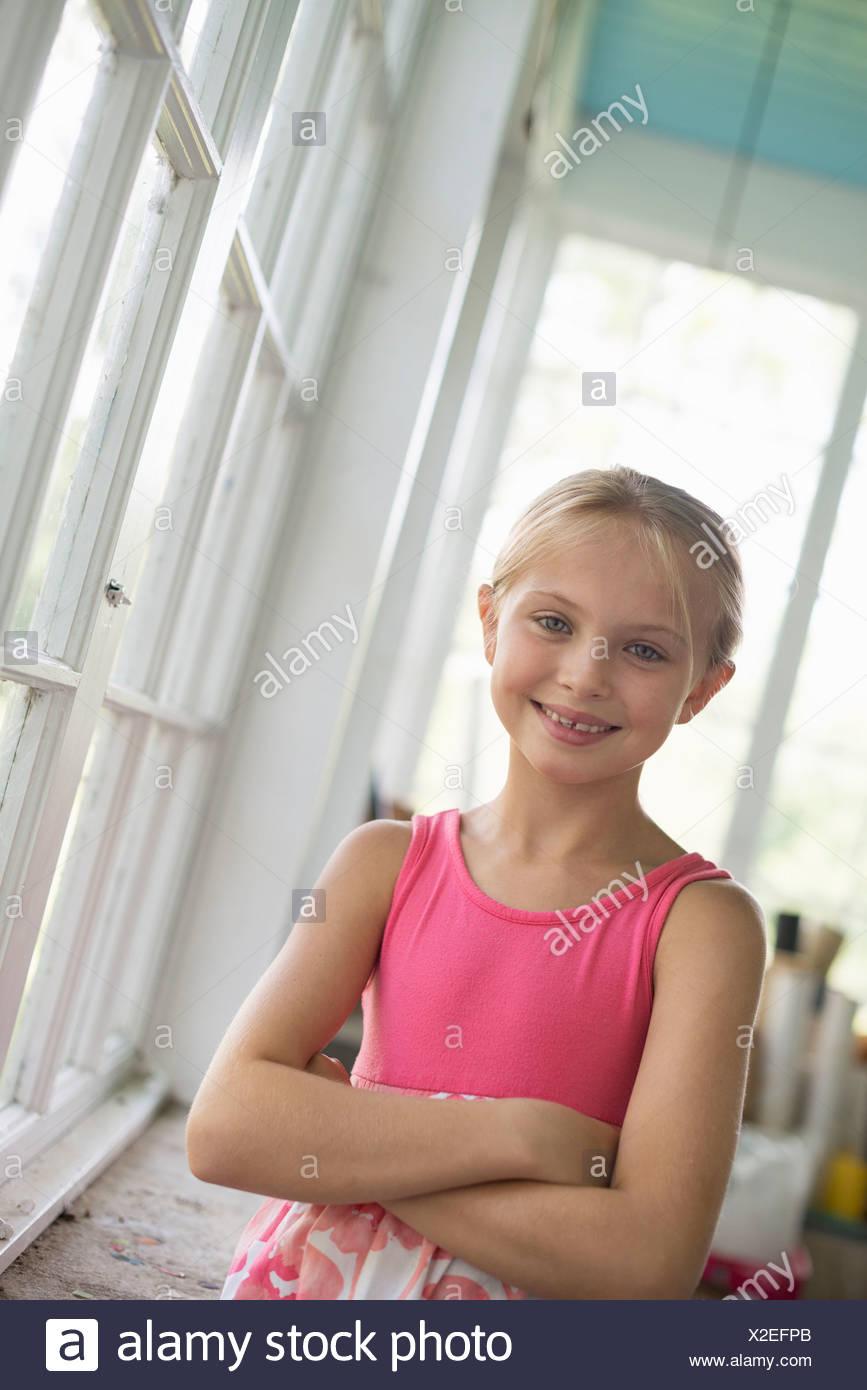 Una giovane ragazza in una cucina che indossa un abito rosa. Immagini Stock