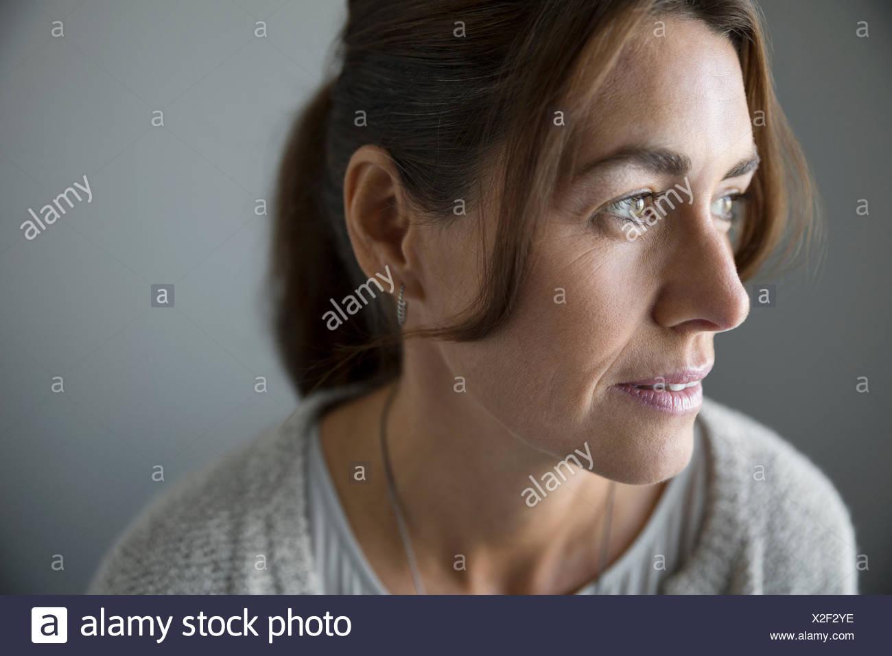 Close up pensieroso brunette donna che guarda lontano Immagini Stock