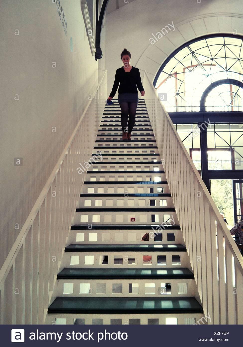 Giovane donna si sta spostando verso il basso le fasi a casa Immagini Stock