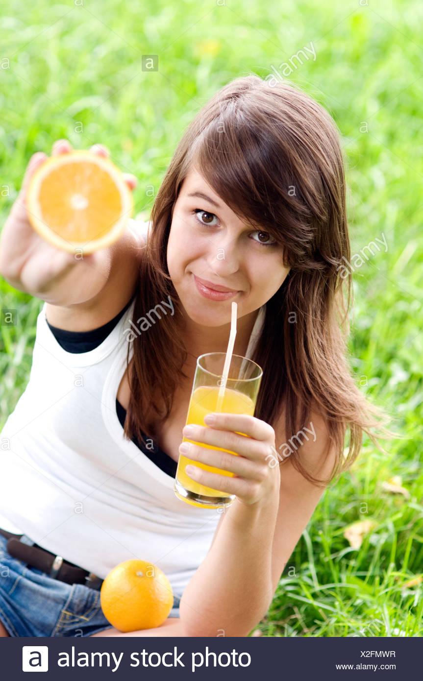 Giovane donna azienda arancione e cocktail di vitamine, Debica, Polonia. Immagini Stock