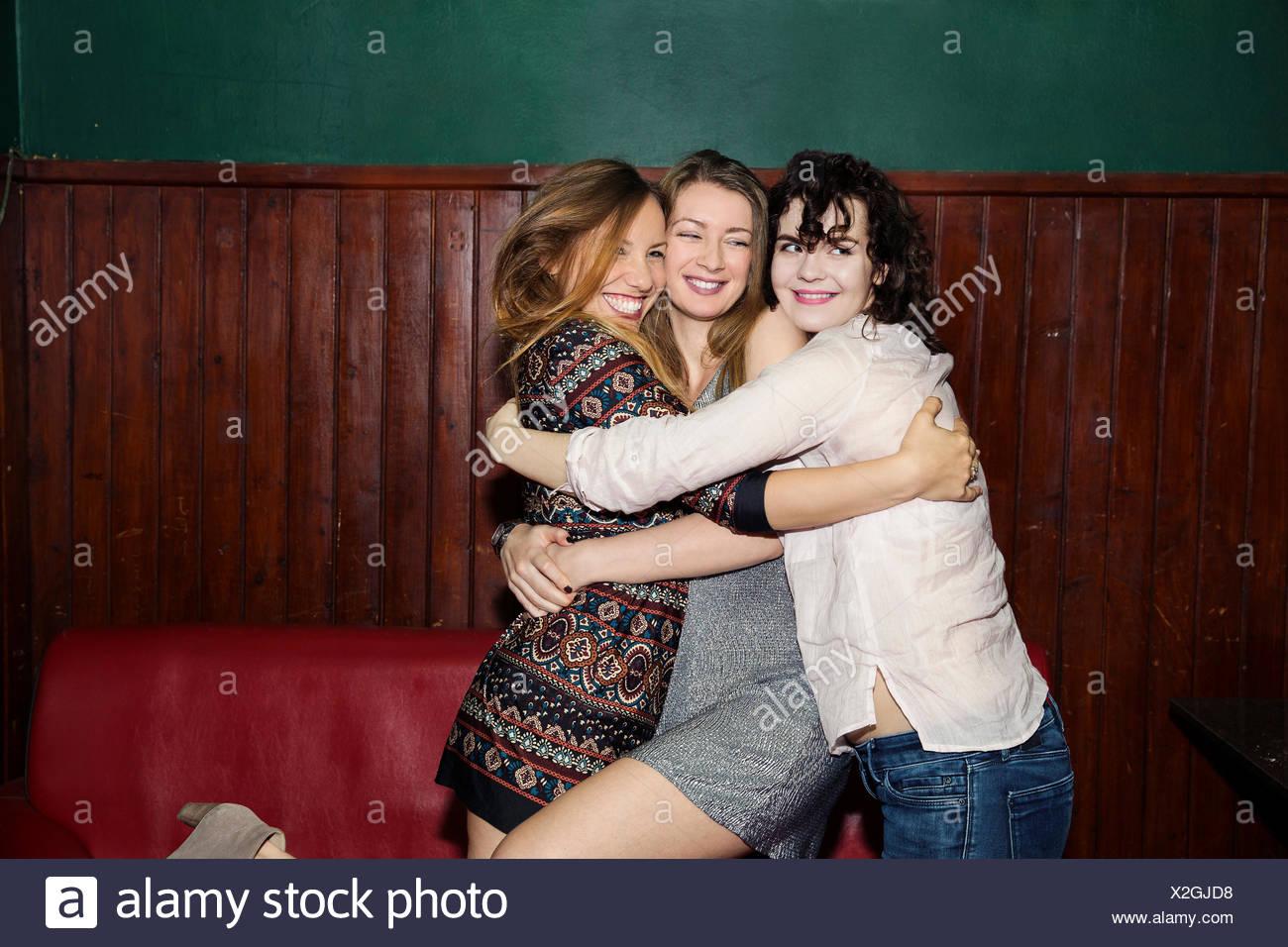 Tre adulti amici femmina avente un gruppo abbraccio in bar Immagini Stock