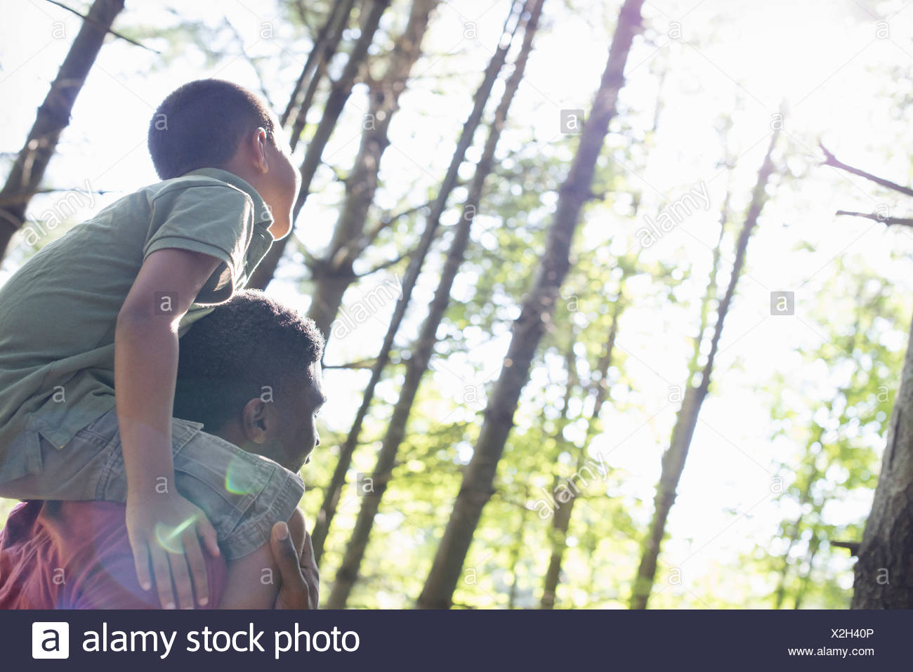 Un ragazzo seduto su di suo padre a spallamenti Immagini Stock