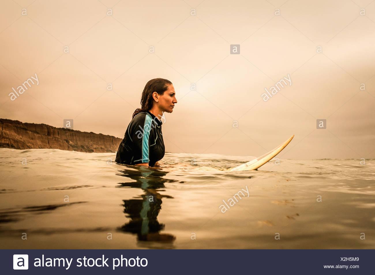 Giovane donna in mare con la tavola da surf, profilo Immagini Stock
