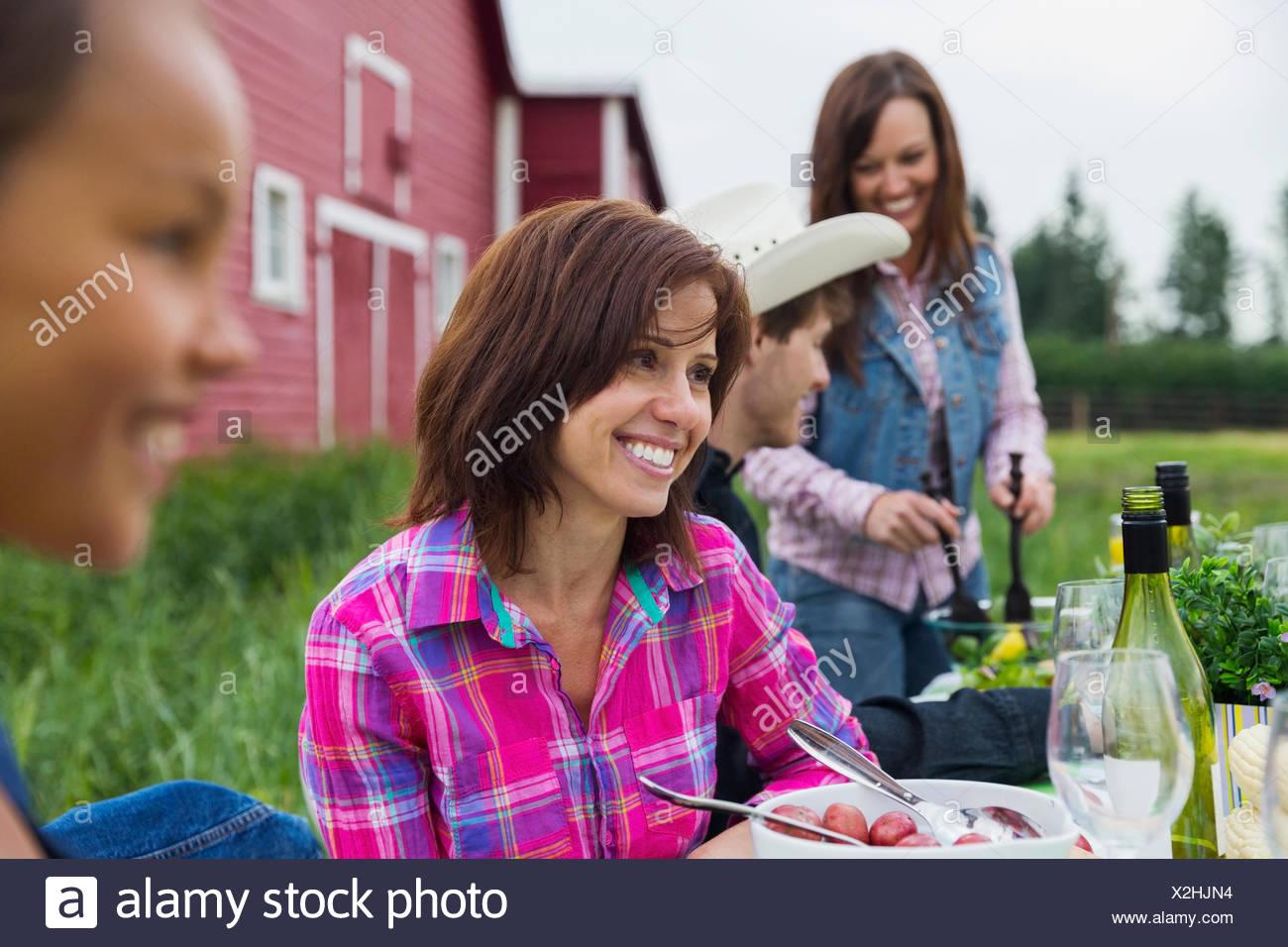 Donna godendo cena di famiglia al di fuori di un fienile Immagini Stock