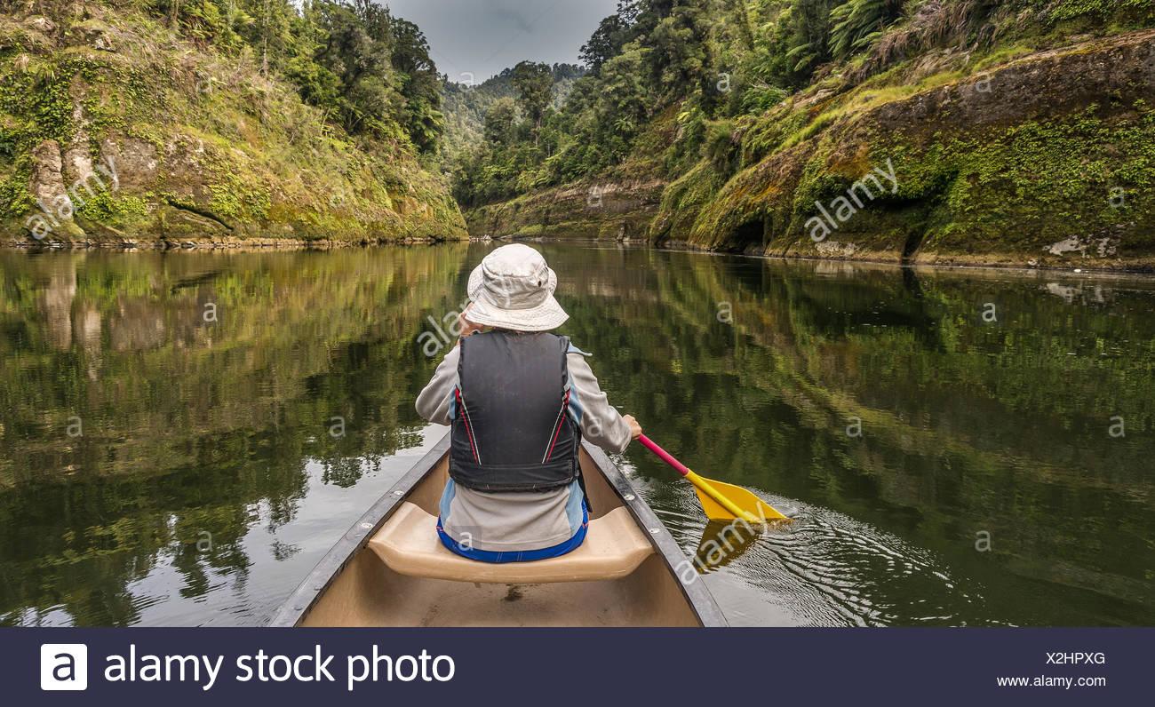 Donna in canoa sul fiume Whanganui, Isola del nord, Nuova Zelanda Immagini Stock