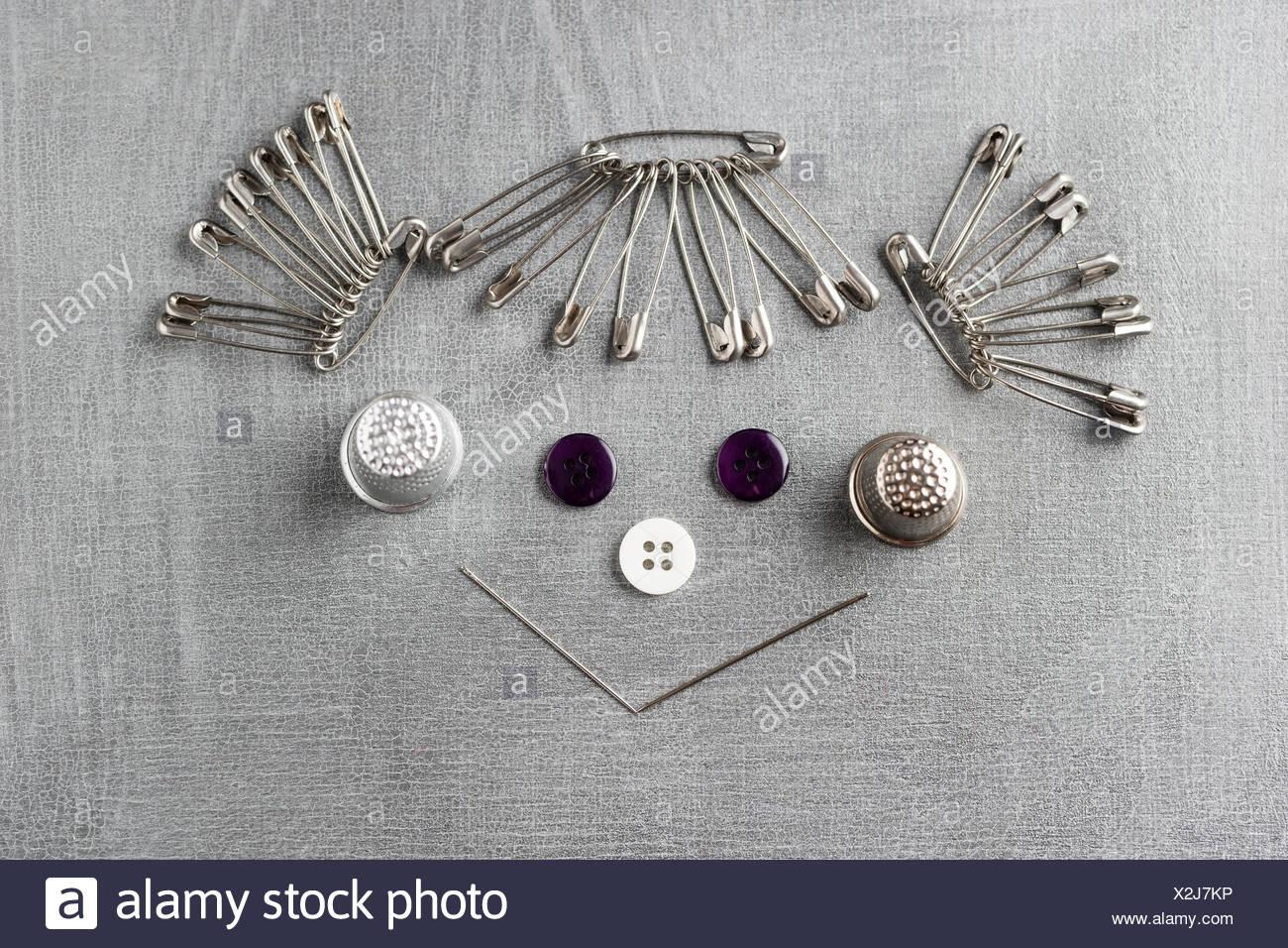 La faccina sorridente di una ragazza costruito di elementi di cucitura su sfondo grigio Immagini Stock