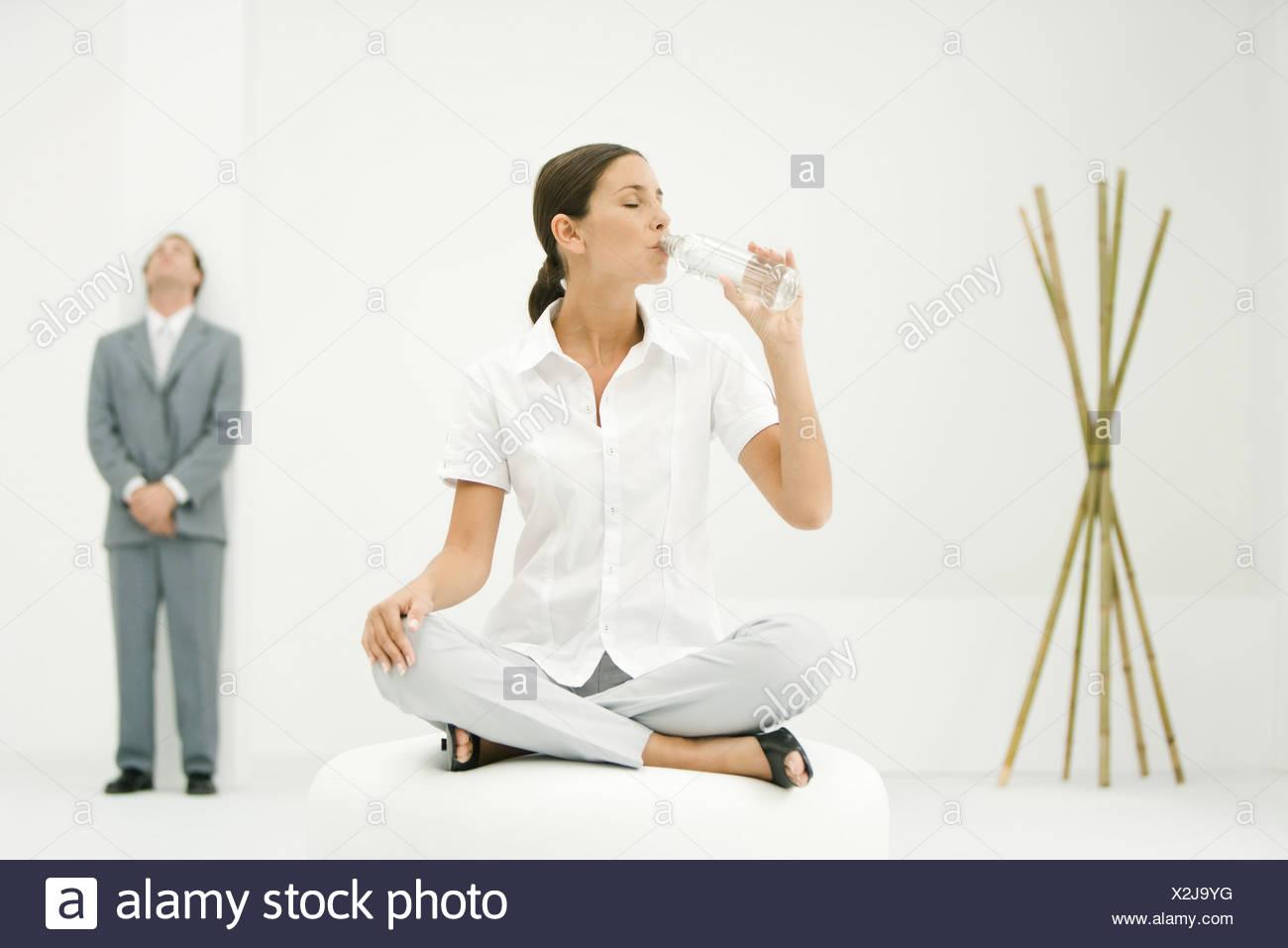 Professional donna seduta su ottomano, bevendo acqua in bottiglia, imprenditore e bambù in background Immagini Stock