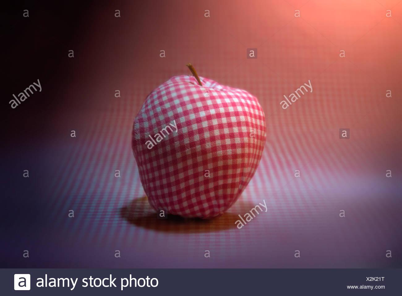 Apple coperto in materiale a scacchi sul materiale a scacchi sfondo Foto Stock
