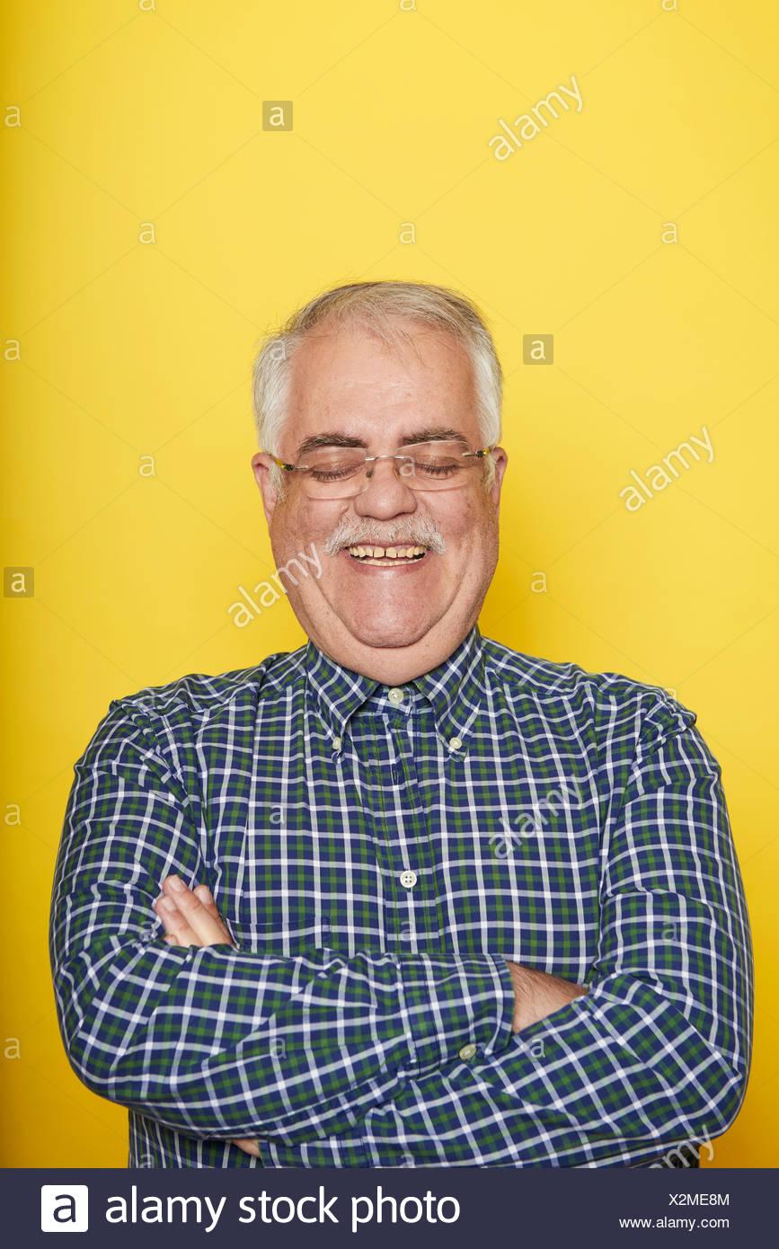 Ritratto di sorridere senior uomo con le braccia incrociate e gli occhi chiusi di fronte a sfondo giallo Immagini Stock