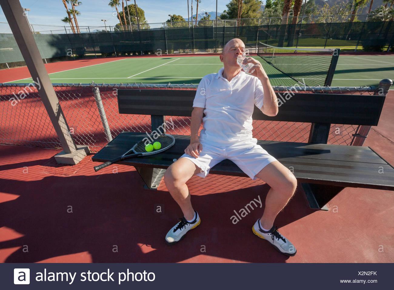 Senior tennista acqua potabile mentre vi rilassate sulla corte Foto Stock