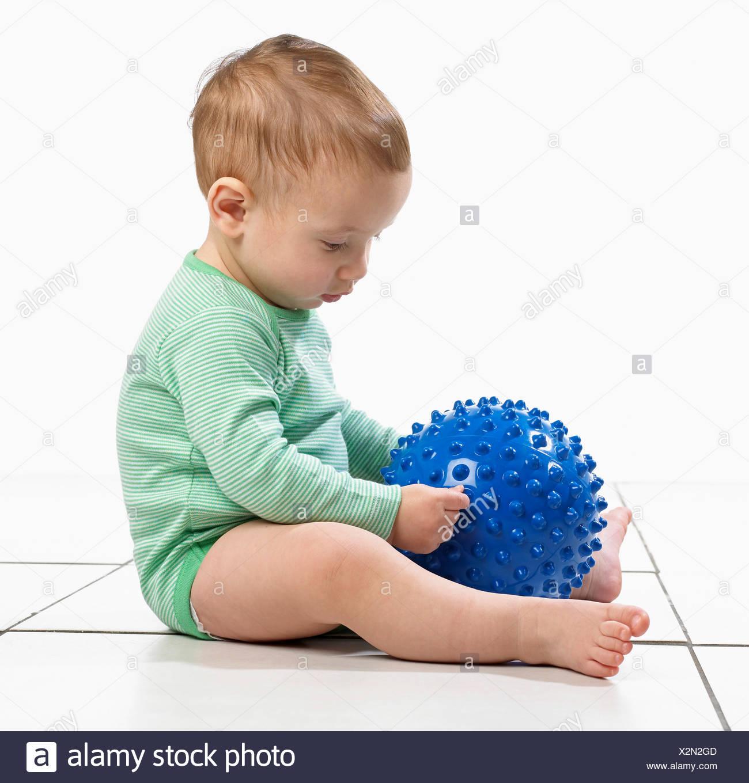 Baby boy (12,5 mesi) seduta tenendo un accidentato giocattolo a sfera Immagini Stock