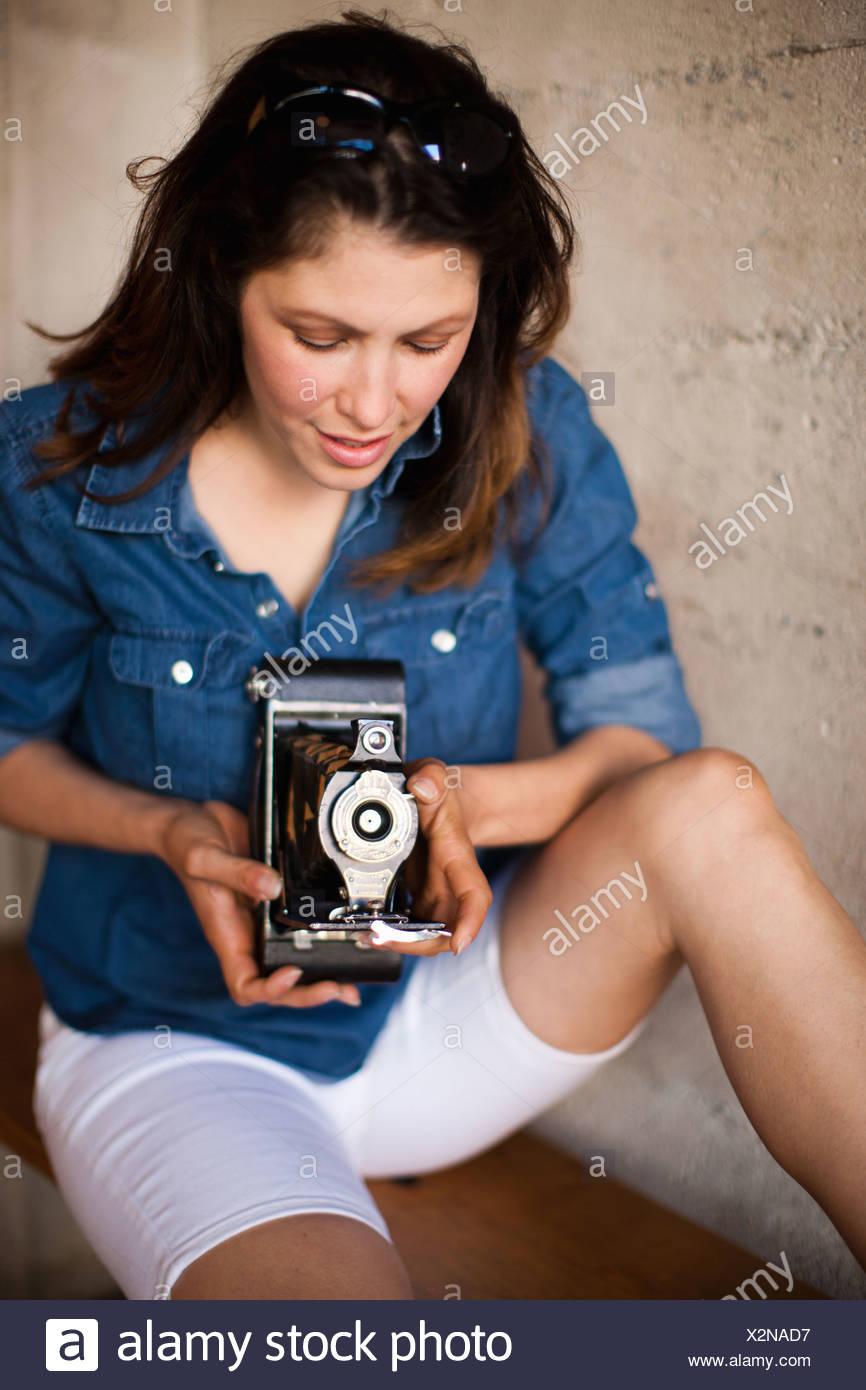 Metà donna adulta utilizzando vintage fotocamera medio formato Immagini Stock