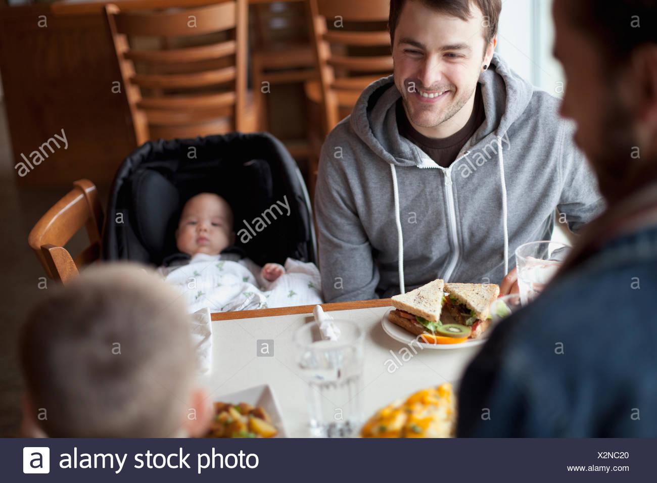 Padri godendo il pranzo con figli giovani Immagini Stock