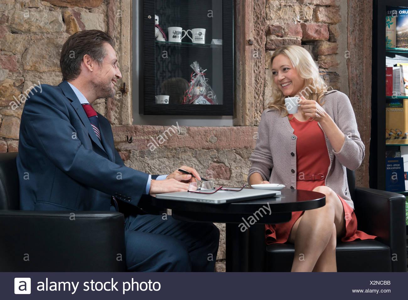L uomo e la donna al tavolo nella lobby dell'albergo, bere un espresso, Sorriso, contatto visivo, flirt Immagini Stock