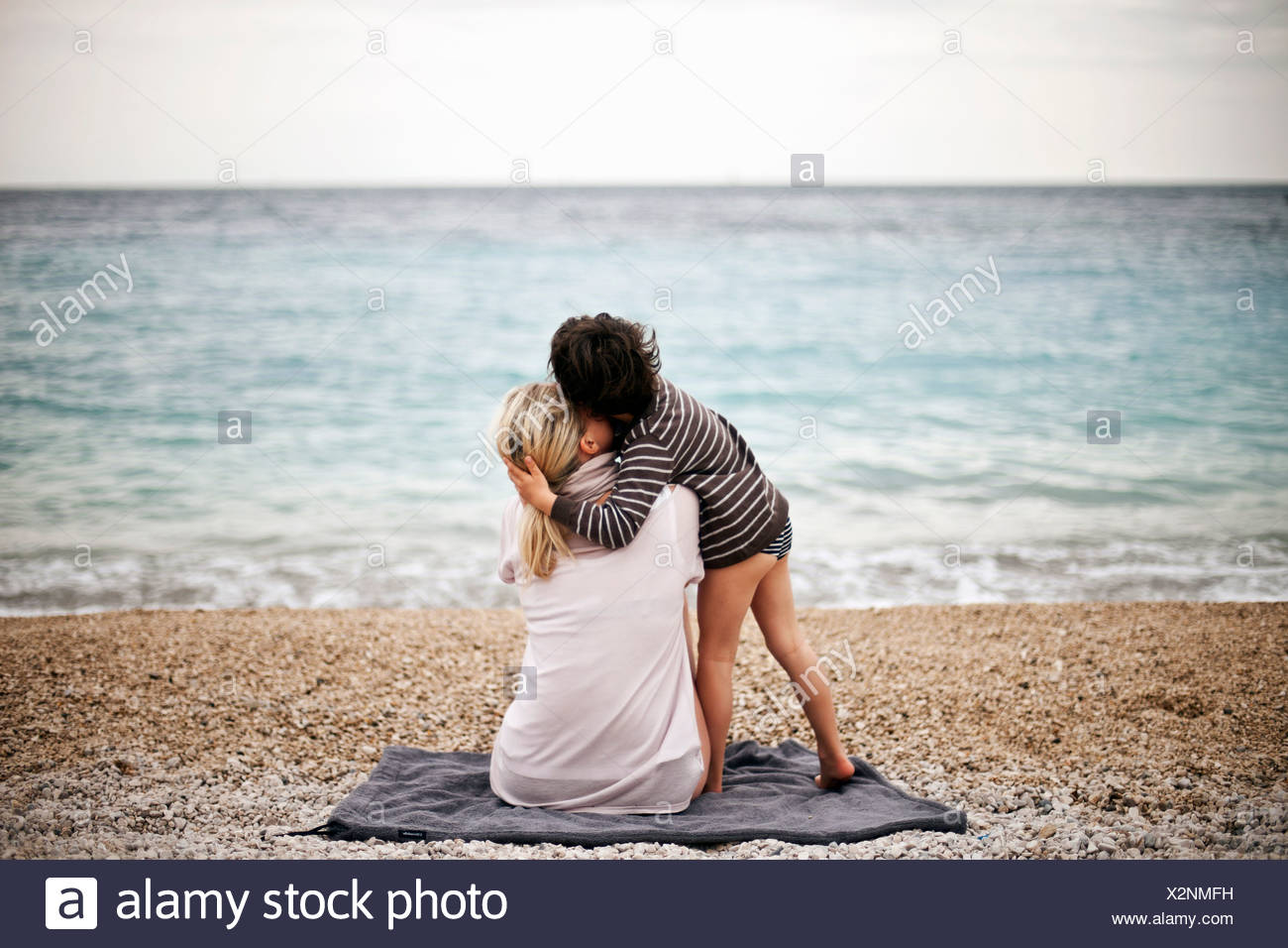 Ragazzo abbracciando la madre su una spiaggia, vista posteriore Immagini Stock