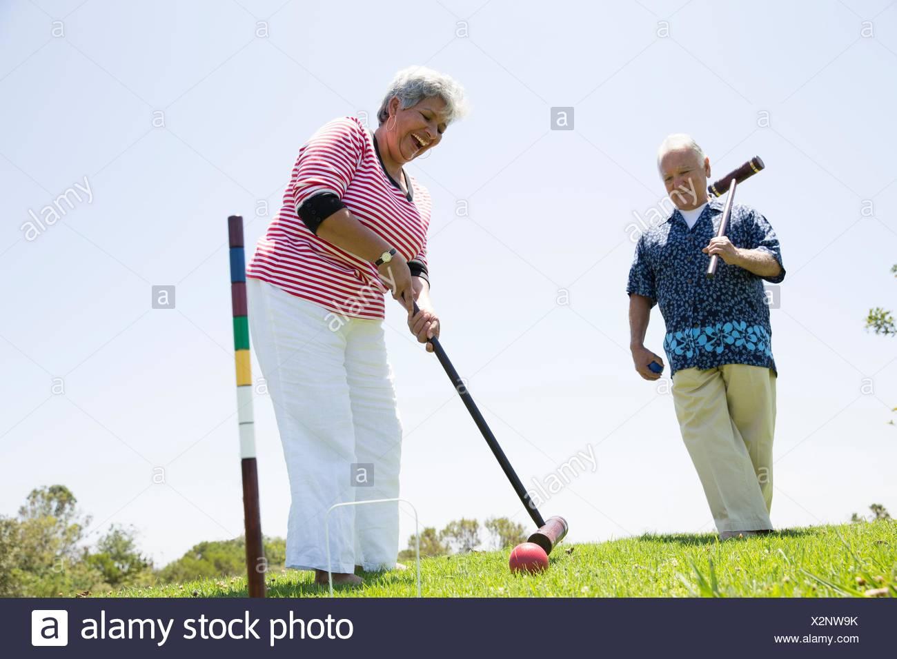 Coppia senior giocando croquet, all'aperto Foto Stock