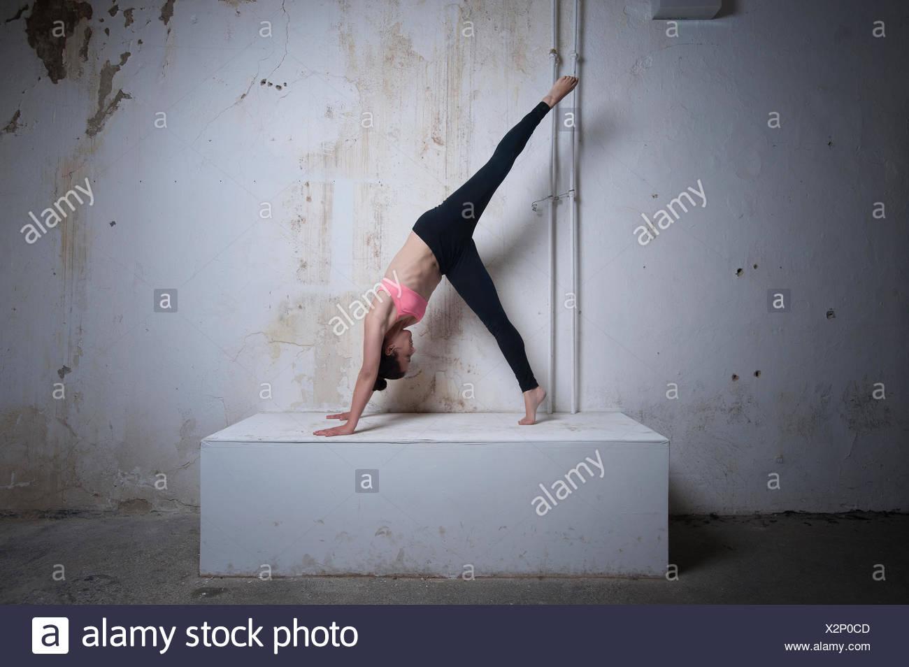 Metà donna adulta praticando uno zampe rivolta verso il basso la posizione del cane sul blocco di calcestruzzo, Monaco di Baviera, Germania Immagini Stock