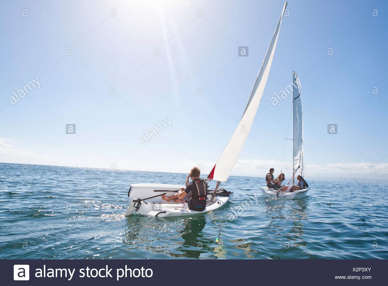 Giovani amici adulti racing a vicenda nelle barche a vela Immagini Stock