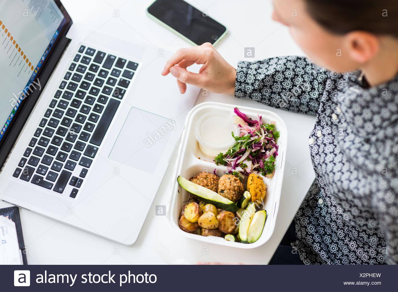 Donna di mangiare bento sul lavoro. Immagini Stock
