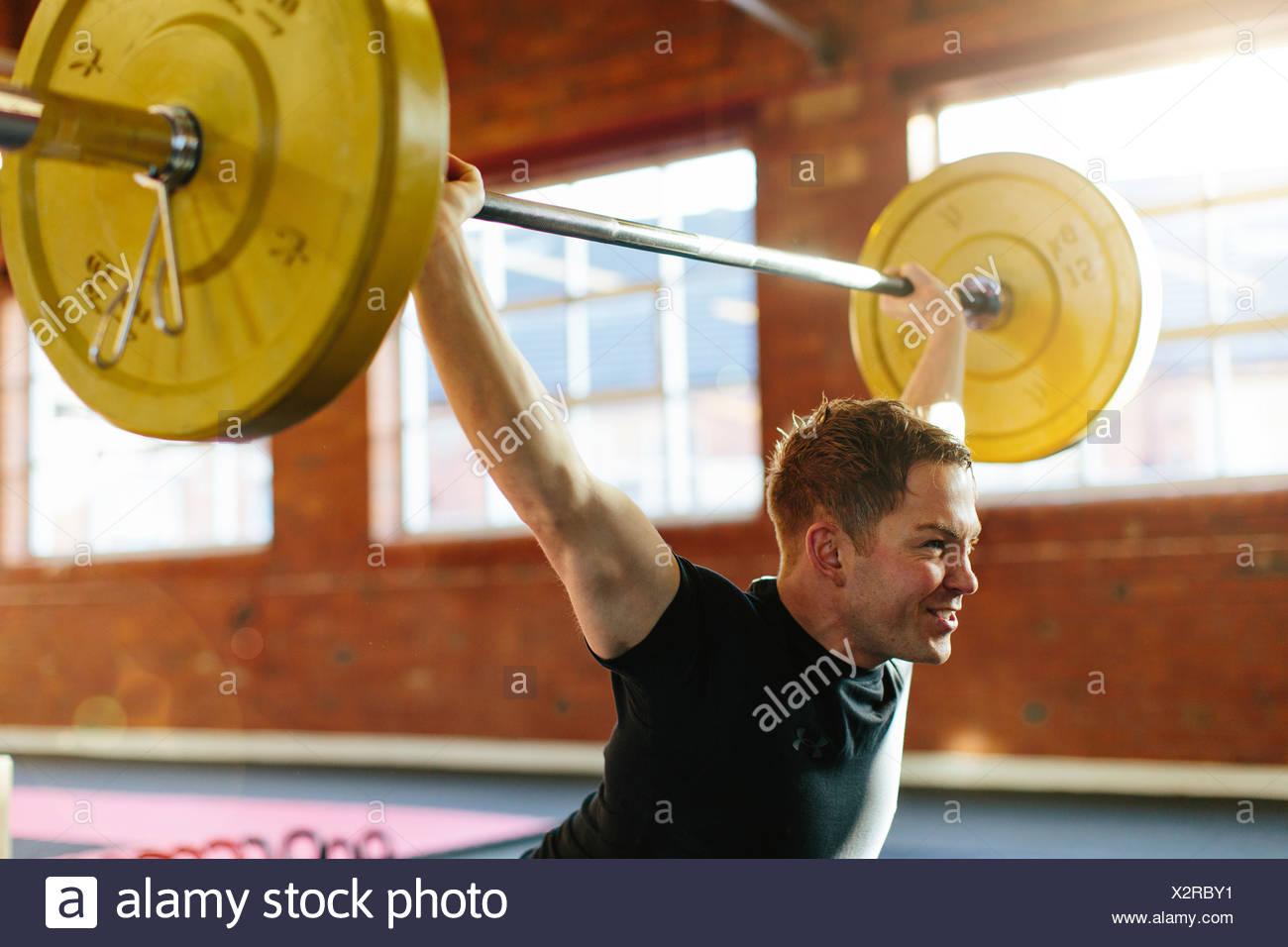 L'uomo il sollevamento pesi nella palestra Immagini Stock