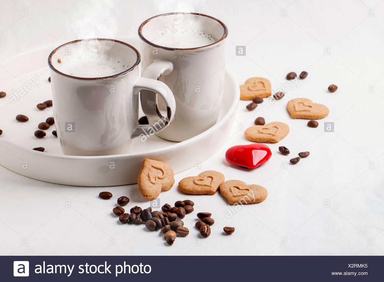 Due tazze di cappuccino servito con spezie e cookie come cuori e un cuore rosso su bianco tessile. Immagini Stock